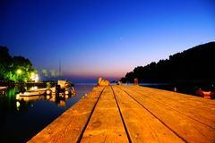 Agnontas beach and bay at night, Greece. Small wooden pier at Agnontas beach, used by fishermen and locals stock photo