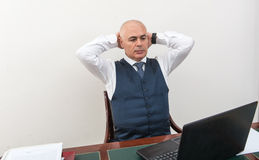 An agonising business man, in crisis, in front of his pc. Stock Photos