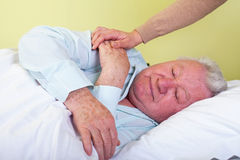 Agonized elderly man. Picture of a sick elderly man in bed with his caregiver stock photos