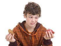 Agonizing choice. Eying the apple but wishing for cookie Stock Images