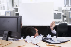 Agony of defeat with copyspace. Young businessman with his face down while holding a white copyspace at his office Royalty Free Stock Photo