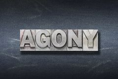 Agony word den. Agony word made from metallic letterpress on dark jeans background royalty free stock image