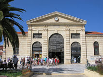 Agora, covered market of Chania, Crete, Greece. Group of tourists go to covered market of Chania town. Municipal Market of Chania is known as Agora. It was built Royalty Free Stock Photography