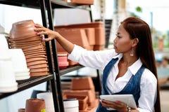 Agrónomo bastante asiático de la mujer de los jóvenes con la tableta que trabaja en invernadero que comprueba el inventario del a fotografía de archivo libre de regalías