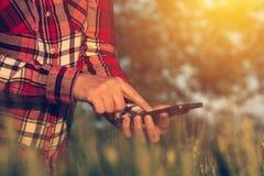 Agrónomo que usa el teléfono elegante app móvil para analizar el developm de la cosecha imagenes de archivo