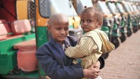 Agra, Índia - 12 de dezembro de 2018: Um menino pequeno do mendigo guarda um bebê em seus braços na perspectiva de um riquexó filme