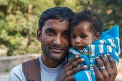 AGRA, ÍNDIA - EM DEZEMBRO DE 2012: Família indiana, pai que guarda a filha em seu regaço Fotos de Stock Royalty Free