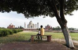 AGRA ΙΝΔΊΑ 2016: Δύο αγόρια που κάθονται κάτω από το δέντρο και που απολαμβάνουν την καταπληκτική θέα Taj Mahal, Agra, Ινδία στοκ εικόνες