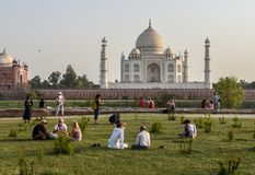 Taj Mahal palace in Agra city, India. Agra, India – March 15 2017: Tourist people  sitting and enjoying at the backyard gardens of famous Taj Mahal palace in Royalty Free Stock Image