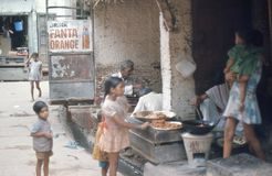 1975. India. Children buying sweet cakes. Agra. The picture shows some children who wants to buy some fresh made cakes Royalty Free Stock Photo