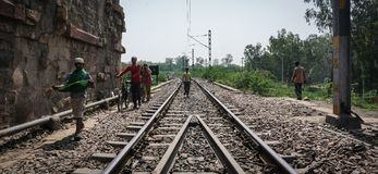 People walking on railway track in Agra, India. Agra, India - Jul 13, 2015. People walking on railway track in Agra, India. Agra is a city on the banks of the Stock Image