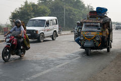 Overloaded motorcycles and tuk-tuks on covered by haze route, Ce. AGRA, INDIA - NOVEMBER 15: Overloaded motorcycles, cars and tuk-tuks drive on covered by haze Stock Photos