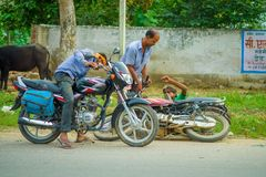 AGRA, INDIA - SEPTEMBER 19,M 2017: Unidentified man rides a motorcycle, while other man is helping his friend that Stock Photo