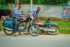 AGRA INDIA, WRZESIEŃ, - 19, M 2017: Niezidentyfikowany mężczyzna jedzie motocykl, podczas gdy inny mężczyzna pomaga jego przyjaci Zdjęcia Stock