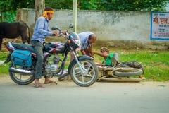 AGRA INDIA, WRZESIEŃ, - 19, M 2017: Niezidentyfikowany mężczyzna jedzie motocykl, podczas gdy inny mężczyzna pomaga jego przyjaci Zdjęcie Royalty Free