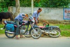 AGRA INDIA, WRZESIEŃ, - 19, M 2017: Niezidentyfikowany mężczyzna jedzie motocykl, podczas gdy inny mężczyzna pomaga jego przyjaci Zdjęcie Stock