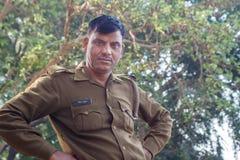AGRA INDIEN - DECEMBER 2012: Indisk polis som ser kameran på en flodbank arkivbilder