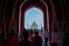 Agra Indien - September 20, 2017: Folkmassan av folk som går till och med en enorm dörr med Taj Mahal i horizonten, är Arkivfoto