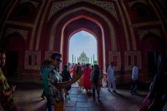 Agra Indien - September 20, 2017: Folkmassan av folk som går till och med en enorm dörr med Taj Mahal i horizonten, är Arkivbild