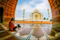 Agra Indien - September 20, 2017: Oidentifierat kvinnasammanträde i golvet och enjooying av den härliga sikten av Tajen Arkivfoton