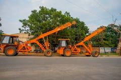 Agra Indien - September 20, 2017: Slut upp av stora orange konstruktionsmaskiner som parkeras i en sida av en gata i Agra Royaltyfri Foto
