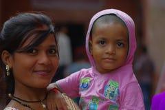 Agra, la India - 20 de septiembre de 2017: Retrato de un adolescente hermoso que detiene a su pequeña hermana en sus brazos, mira Foto de archivo libre de regalías