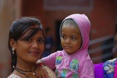 Agra, la India - 20 de septiembre de 2017: Retrato de un adolescente hermoso que detiene a su pequeña hermana en sus brazos, mira Imagen de archivo libre de regalías