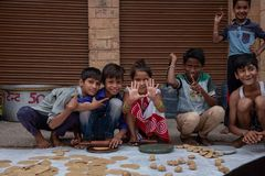 A group of kids pose for a photo while rolling roti. royalty free stock images