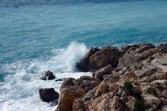 Agradável, França, em março de 2019 Mar bonito de turquesa, montanhas no embaçamento e a terraplenagem de Promenade des Anglais e fotos de stock royalty free