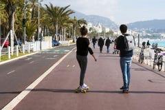 Agradable, Francia, marzo de 2019 Dos personas jovenes: un muchacho y un paseo de la muchacha un monopatín a lo largo de la 'prom imágenes de archivo libres de regalías