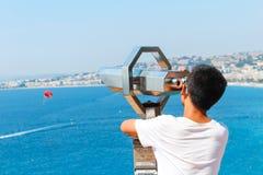 Agradable, Francia - 16 09 16: Muchacho que mira a través de los prismáticos en un paracaídas del vuelo en un mar hermoso en Niza Fotos de archivo