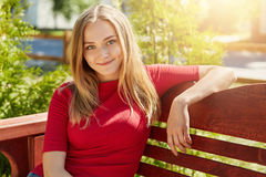 Agradable-mirando a la hembra rubia que lleva el suéter rojo casual que se sienta el banco de madera cómodo contra el fondo verde Foto de archivo