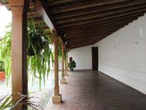 Pasillo Abierto De Casa Colonial Con Helechos Pisos En Piedra. Agradable patio colonial tradicional con áreas techadas en bambú y madera y plantas que le stock images