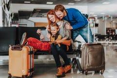 Agradavelmente a família está tendo o divertimento com o touchpad no aeroporto imagens de stock royalty free