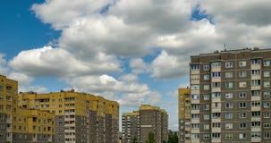 Agrafe de laps de temps des nuages de roulement pelucheux blancs dans la perspective des immeubles ? plusiers ?tages jaunes clips vidéos