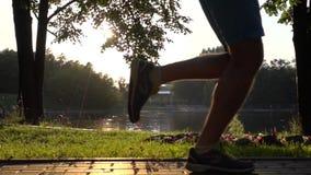 Agrafe de steadicam de mouvement lent de parc de coucher du soleil et coureur écrivant et partant du cadre clips vidéos