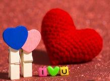 Agrafe en bois de coeur avec le coeur rouge de fil et je t'aime de la perle colorée sur l'espace rouge de copie de plancher et de Photographie stock