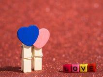 Agrafe en bois de coeur avec le texte d'amour de la perle colorée sur le plancher et le fond rouges Copiez l'espace pour le texte Images stock