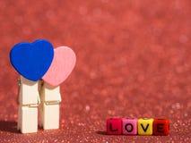 Agrafe en bois de coeur avec le texte d'amour de la perle colorée sur le plancher et le fond rouges Copiez l'espace pour le texte Photo stock