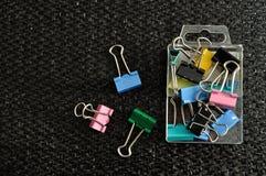 Agrafes colorées de reliure dans un récipient Photographie stock