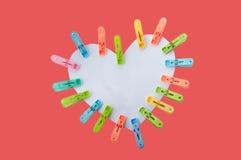Agrafes multicolores de forme de coeur sur le fond rouge Photo stock