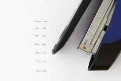 Agrafeuse et agrafes bleues avec le papier Photos stock