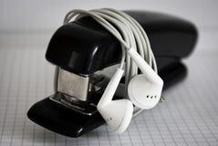 Agrafeuse noire verrouillée par les écouteurs blancs Photographie stock
