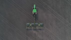 Agrargeschäft, Luftgesamtlänge des modernen Traktors behandelt das Land auf dem Gebiet unter Verwendung der Pflüge am Frühling stock video