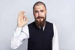 agree Knappe zakenman die met baard en stuursnor camera met O.k. teken bekijken stock foto