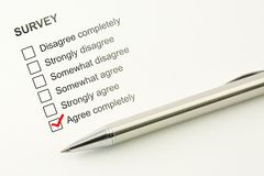 Agree survey feed back. Agreement concept. Marked checkbox with a pen on paper background. Agree survey feed back. Agreement concept. Marked checkbox between Stock Photo