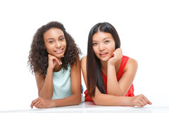 Agreeable girls lying on the floor Stock Images