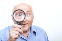 Agreeable grandfather keeping loupe Royalty Free Stock Photo