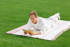 Agreeable man lying on the grass Stock Images