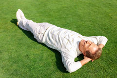 Agreeable man lying on the grass Stock Image